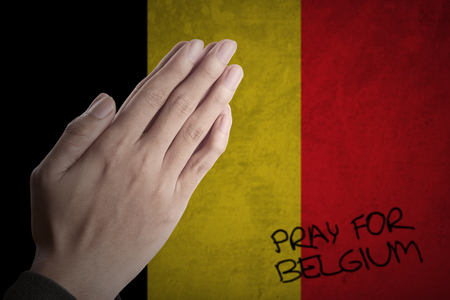 extremist: Close up of hands pose praying for Belgium in front of Belgian flag
