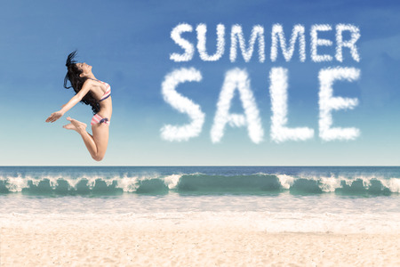 Summer sale clouds and woman jumping at beach Stock Photo