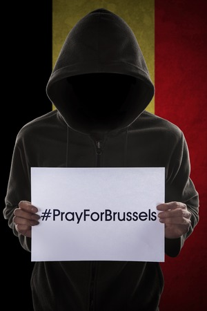 extremist: Picture of a man invites to pray for Brussels while wearing a hoodie in front of Belgian flag Stock Photo