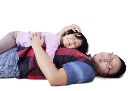 caress: Portrait of a young father lying on the floor while caress his daughter, isolated on white background