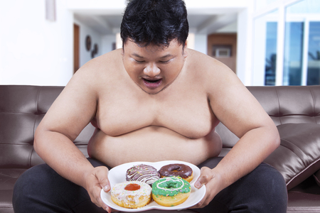 hungry: Image of hungry overweight person sitting on the sofa while holding donuts at home