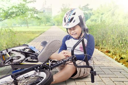 Ritratto di bambino che piange mentre si tiene il ginocchio dopo essere caduto dalla moto al parco