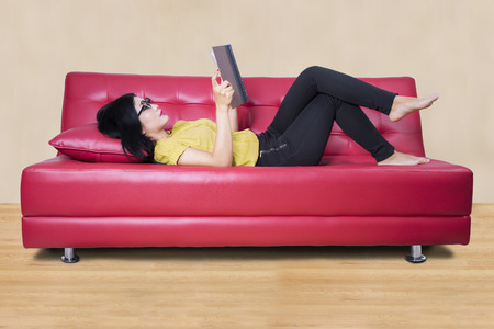 storybook: Beautiful young woman reading a storybook while lying on the couch at home Stock Photo