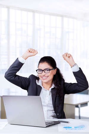 woman work: Picture of Indian businesswoman celebrates her success with arms up in the office, wearing formal suit and glasses