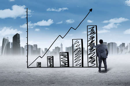 unemployment rate: Male worker making a growing graph with upward arrow, shot outdoors