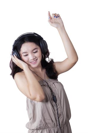 ragazze che ballano: Ritratto di felice ragazza che balla e si ascolta la musica isolato su sfondo bianco
