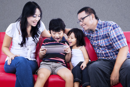 tame: Excited family playing tame on e-tablet with grey background