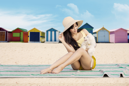 Cheerful young girl and her dog sitting on the mat at the beach with the beach huts background