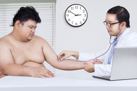 asian adult: Portrait of male doctor using a stethoscope to check patient heartbeat at hospital Stock Photo