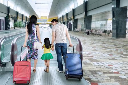 maletas de viaje: Vista trasera de la familia feliz caminando en el pasillo del aeropuerto, mientras que llevar una maleta para viajar y tomarse de las manos juntas