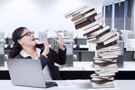 office workers: Indian businesswoman looks tired and tries to hold a pile of falling books in the office with a notebook on the table