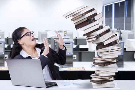 Indiase zakenvrouw ziet er moe en probeert een stapel dalende boeken te houden in het kantoor met een laptop op de tafel