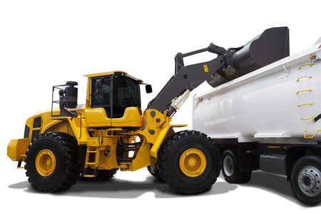 isolated on yellow: Image of a yellow backhoe using a scoop to load soil into a truck, isolated on white background Stock Photo