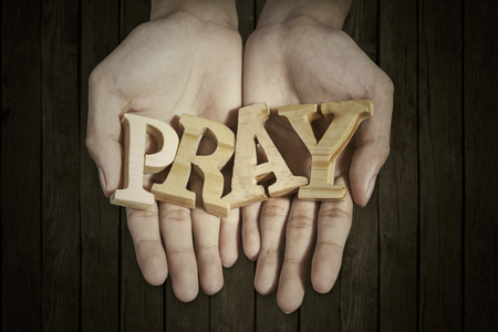 trust in god: Close up of two prayer hands holding a word of pray with wooden background