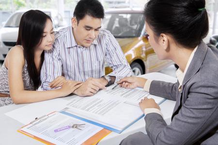 firmando: Retrato de dos compradores de automóviles lectura de un documento de la norma de crédito para comprar un coche en la sala de exposición