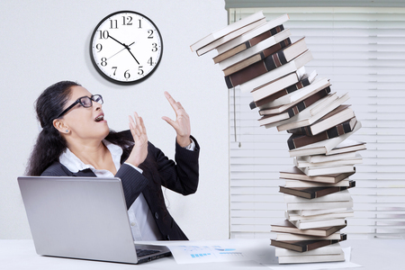 working overtime: Indian young businesswoman working overtime and tries to hold a pile of falling books Stock Photo