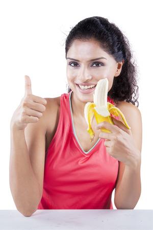 comiendo platano: mujer joven sana que sonríe a la cámara mientras sostiene un plátano y mostrando el pulgar hacia arriba, aislado en el fondo blanco Foto de archivo