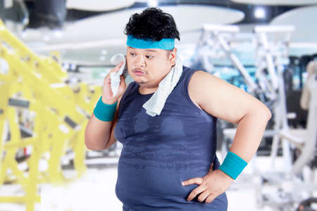 wiping: Exhausted man after workout and wiping his sweat at gym