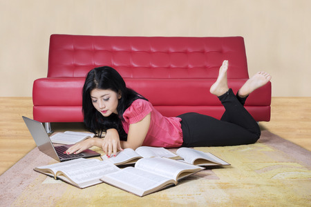 Picture of a pretty female student doing homework with a laptop and books on the carpet at home