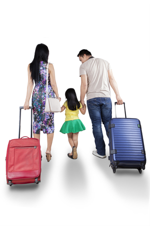 holding hands while walking: Happy family walking in the studio while carrying suitcase for traveling and holding hands together Stock Photo