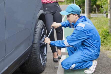 Young male mechanic wearing uniform, changing a car tyre with his client on the road