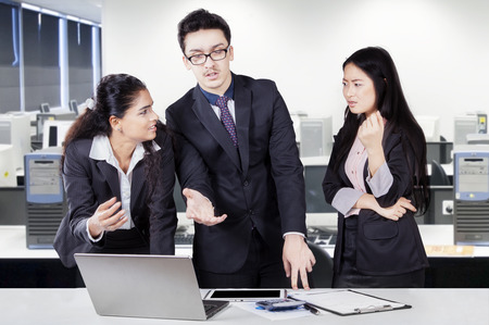 debating: Group of three multiracial workers working in the office while standing and debating in a business meeting