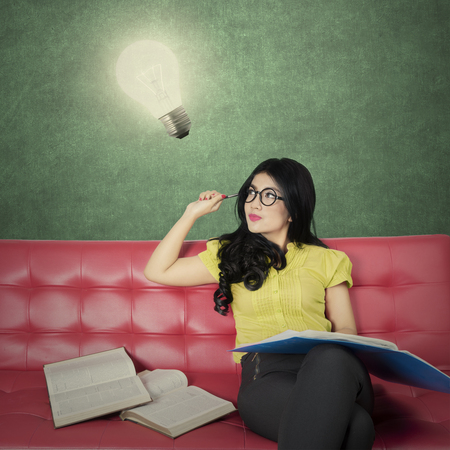 red couch: Portrait of a creative female student reading books on the sofa while looking at a bright light bulb Stock Photo