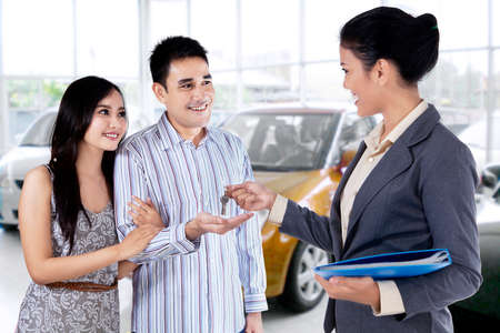 servicio al cliente: Retrato de pareja feliz conseguir una llave del coche de un concesionario de coches en la sala de exposición