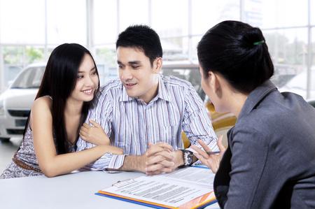 Beeld van twee jonge autokopers bespreken met een vrouwelijke auto dealer in de showroom Stockfoto
