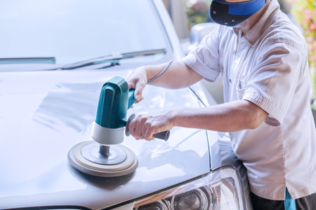 Image of male workshop worker using an auto polisher to polish the car body