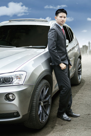 selling service: Portrait of successful male entrepreneur wearing formal suit and standing near a new luxury car