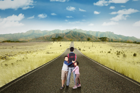 two children: Portrait of two happy children hugging their father on the countryside road with a mountain view Stock Photo