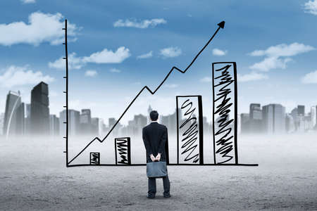 unemployment rate: Male employee holding a briefcase and look at a growing chart with upward arrow