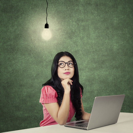 imagining: Young businesswoman working with laptop and wearing glasses while imagining an idea under a light bulb Stock Photo