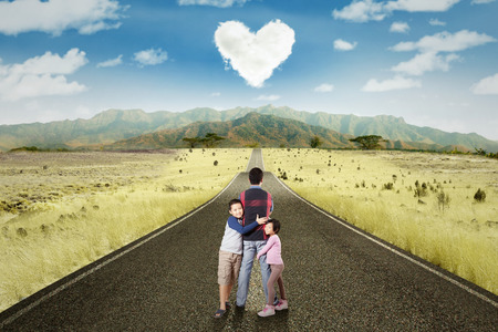 Picture of two children hugging their daddy on the road with cloud shaped heart symbol Stock Photo