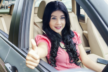 Picture of happy young woman driving a new car while showing thumb up and smiling