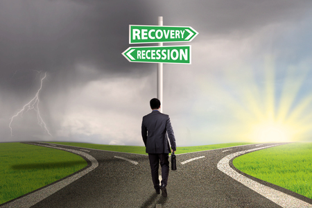 two way: Businessman walking on the road with two words of recession and recovery on the signpost pointing the way Stock Photo
