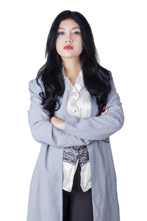 arrogant: Portrait of a young confident businesswoman standing in the studio with folded arms, isolated on white background