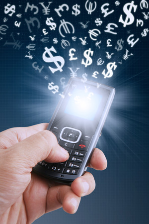 signos de pesos: Human hand holding cellphone with currency symbols fly from a mobile phone