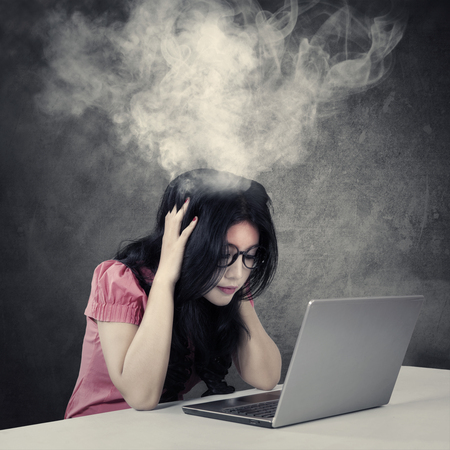 asia women: Picture of a stressful young businesswoman with smoke coming out of her head while working with a laptop