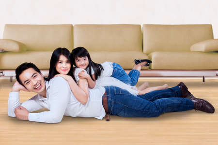 family sofa: Happy Asian family relaxing together while lying on the floor at home and smiling at the camera