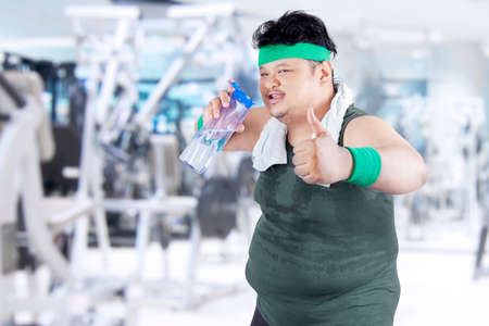 potbelly: Overweight man drinking water while showing thumb up in fitness center