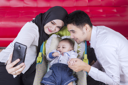arabian: Picture of two young parents with their baby in the stroller, taking selfie picture together at home Stock Photo