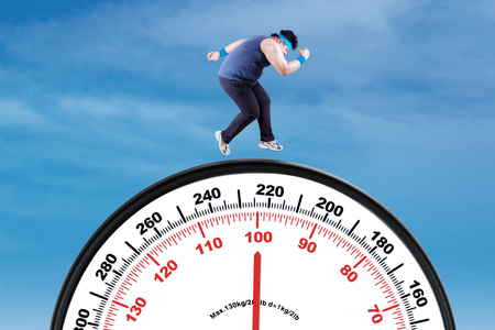 diet plan: Picture of overweight person try to lose weight by workout and running above a big scale