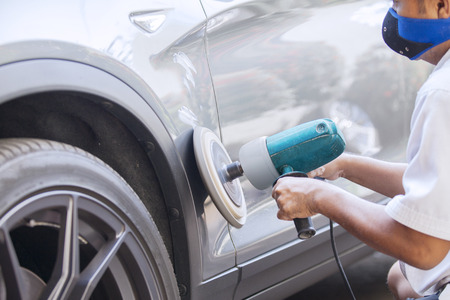 car body: Picture of a male worker polishing a silver car body with an auto polisher machine