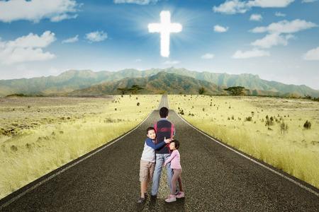 conclusion: Dos niños lindos abrazos a su padre en el camino con una cruz en el cielo