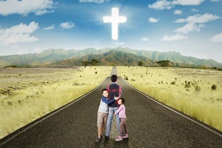 finding: Two cute children hugging their father on the road with a cross sign on the sky