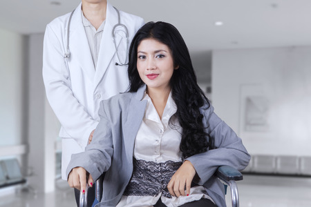 patient care: Pretty female patient with long hair, sitting on the wheelchair with her doctor in the hospital corridor