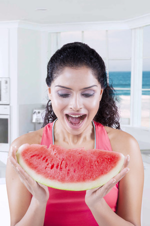 beach window: Picture of happy Indian woman holding and eating slice of fresh watermelon at home with beach background on the window