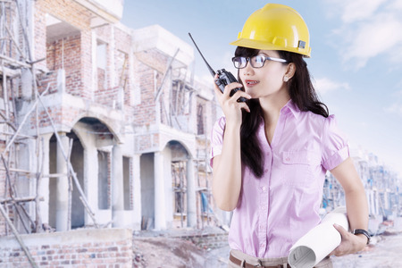 construction workers: Young female contractor wearing helmet and holding a blueprint at the residential site while talking on the walkie-talkie